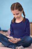 Flicka med flätade trådar som sitter på säng genom att använda smartphonen Arkivfoton