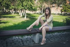 Flicka med flödande hår i korta kortslutningar och skor med häl som sitter på en bänk royaltyfria bilder