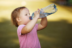 Flicka med flaskan av mineralvatten Royaltyfri Foto