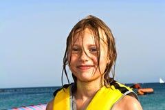 Flicka med flytvästen på stranden Arkivbild