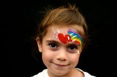 Flicka med framsidan som målas med regnbågen Royaltyfri Foto