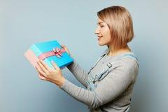Flicka med gåvaasken i hennes händer på en blå bakgrund Arkivbilder