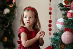 Flicka med gåvor nära en julgran Arkivbild