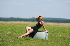 Flicka med gammal tv på mitt av fälten Arkivfoto