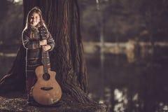 Flicka med gitarren i parkera arkivfoto