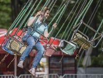 Flicka med glädjeritt på karusellen i nöjesfält Royaltyfri Foto