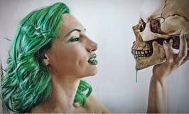 Flicka med grönt hår som rymmer en skalle royaltyfri foto