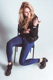 Flicka med grungestilsammanträde i stolen Royaltyfri Foto