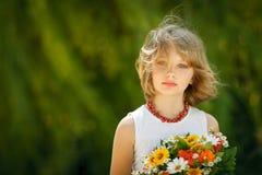 Flicka med gruppen av vildblommor utomhus Arkivfoto
