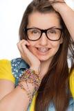 Flicka med hänglsen som bär isolerade geekexponeringsglas arkivfoto