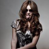 Flicka med hänglsen som ut klibbar tungan Royaltyfri Bild