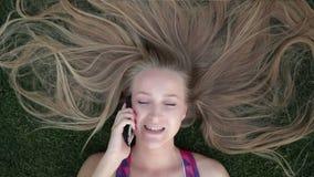 Flicka med härligt blont hår som ligger på gräs lager videofilmer