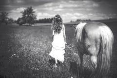 Flicka med hästen på äng Arkivfoto