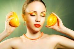 Flicka med hållande orange frukt för härligt smink royaltyfria foton