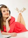 Flicka med hörlurar och datoren som lyssnar till musik Royaltyfria Bilder