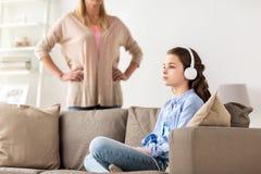 Flicka med hörlurar och den ilskna modern hemma Arkivbild