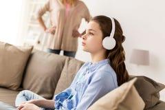 Flicka med hörlurar och den ilskna modern hemma Fotografering för Bildbyråer