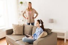 Flicka med hörlurar och den ilskna modern hemma Royaltyfri Bild