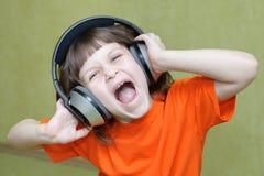 Flicka med hörlurar på head sjunga högt royaltyfria bilder