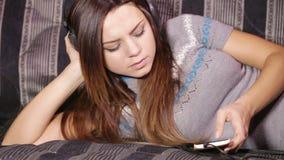 Flicka med hörlurar på soffan arkivfilmer