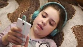 Flicka med hörlurar som lyssnar till musik från smartphonen arkivfilmer