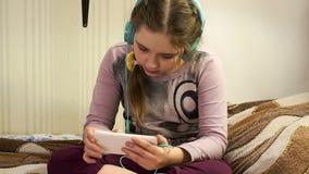 Flicka med hörlurar som lyssnar till musik från smartphonen lager videofilmer