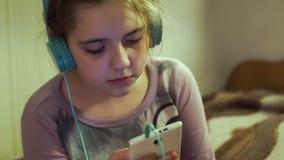 Flicka med hörlurar som lyssnar till musik från smartphonen stock video