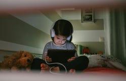 Flicka med hörlurar som ser minnestavlan Arkivfoto