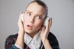 Flicka med hörlurar som uttrycker negativa sinnesrörelser Arkivfoto