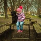 flicka med hans svarta schnauzerhund på en träbänk Arkivfoto