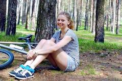 Flicka med hennes cykel i skogen Arkivbilder
