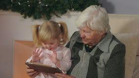 Flicka med hennes farmor som ser minnestavlabilderna lager videofilmer