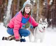 Flicka med hennes gulliga hund i vinterskogen Fotografering för Bildbyråer