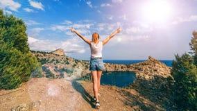 Flicka med hennes händer upp i natur i sommaren mot havet överst av bergen royaltyfria foton