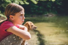 Flicka med hennes hund vid sjön royaltyfri bild