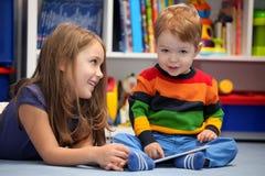 Flicka med hennes lilla broder som använder en digital minnestavladator Royaltyfri Fotografi