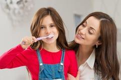 Flicka med hennes moder som borstar tänder fotografering för bildbyråer