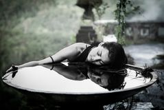 Flicka med hennes reflexion i stor bunke i det mystiska övergav hotellet i Bali Indonesien Arkivfoto