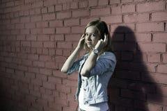 Flicka med hörlurar Fotografering för Bildbyråer