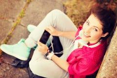 Flicka med hörlurar som lyssnar till musik Arkivfoto