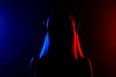 Flicka med hörlurarkonturn Arkivbild