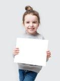 Flicka med hårstrålen som rymmer en vitbok, Royaltyfri Fotografi