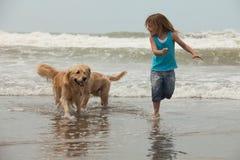 Flicka med hundkapplöpning på stranden Royaltyfria Foton