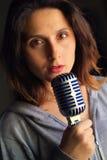 Flicka med hypnotisk blick med en mikrofon Royaltyfria Bilder