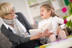 Flicka med intresserade boken för mormor den läsning royaltyfria foton