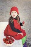 Flicka med jordgubbar Flicka med en röd hatt Fotografering för Bildbyråer
