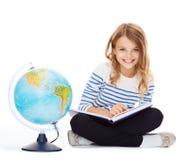 Flicka med jordklotet och boken Royaltyfri Foto