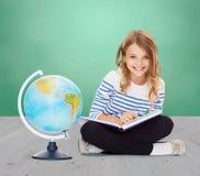 Flicka med jordklotet och boken arkivfoton