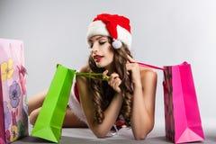 Flicka med jul som shoppar i hatten av Santa Claus Royaltyfri Fotografi
