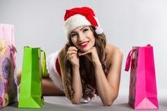 Flicka med jul som shoppar i hatten av Santa Claus Arkivbild